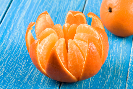 one peeled tangerine on a blue wooden background