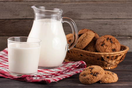 jag: jug and glass of milk with oatmeal cookies in a wicker basket on a wooden background
