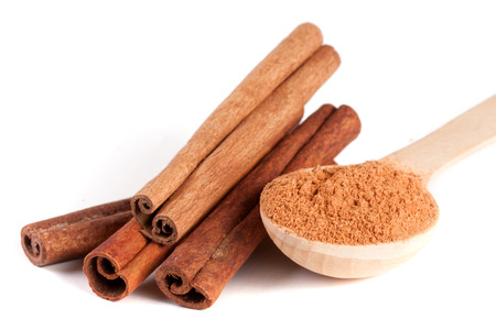 four cinnamon sticks and powder with spoon isolated on white background Banque d'images
