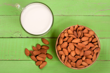 Almond milk in a glass and almonds in a bowl on green wooden background. Top view Stock Photo