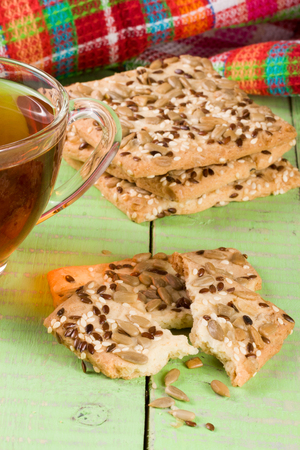 sunflower seeds: crispy bread with seeds of sunflower, flax and sesame seeds with a cup of tea on a green wooden background