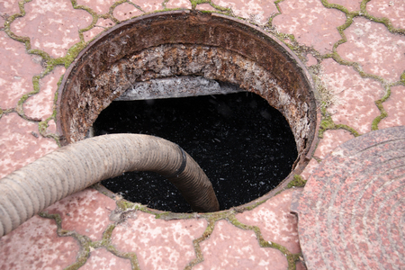pumping sewage from the drain hole. Stock Photo