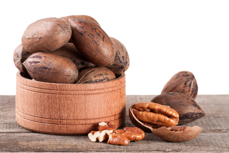 pekan: pecan nuts in a wooden bowl on the old board