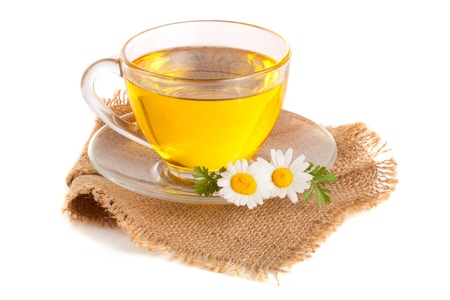 Herbal tea with fresh chamomile flowers on sackcloth isolated on white background Stock Photo