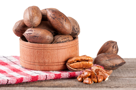 pekan: pecan nuts in a wooden bowl on the old board with white background
