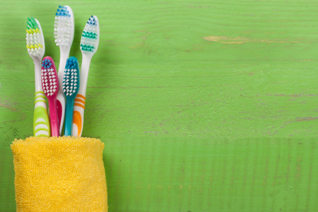 toothbrushes on the green wooden background with copy space for your text. Top view