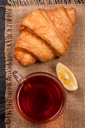 croissant with a cup of tea on sackcloth. Top view. Stock Photo