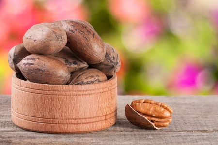 pecan nuts in a wooden bowl on the old board with blurred garden background