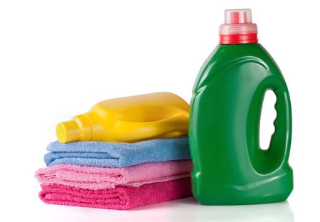 fles wasmiddel en conditioner of wasverzachter met handdoeken geïsoleerd op een witte achtergrond