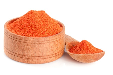 powdered: Ground paprika in a wooden bowl with a spoon isolated on a white background