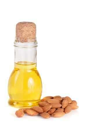 moisturize: Bottle of almond oil and almonds isolated on white background