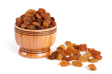 scattering: raisins in a wooden bowl isolated on white background