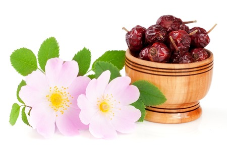 roze: Rosehip flowers with leaf and rosehip berries in a wooden bowl isolated on white background