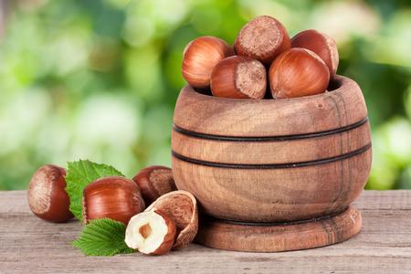 albero nocciolo: Nocciole con foglie in una ciotola di legno su un tavolo di legno con sfondo del giardino sfocato