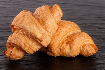 buttered: two croissant on black stone background closeup