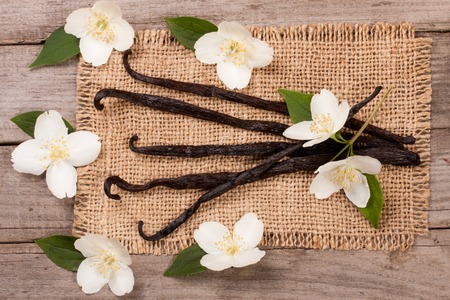 Vanilla sticks with flower and leaf on a old wooden background