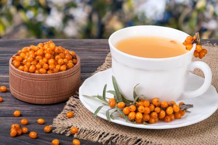 Tea of sea-buckthorn berries on wooden table with blurred garden background