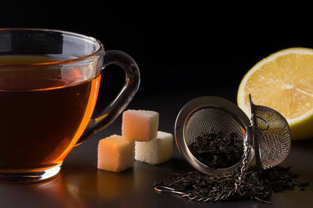 cup of tea with a strainer and  lemon on  dark background Stock Photo