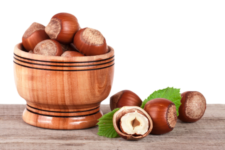 Hazelnuts with leaves in a wooden bowl on a wooden table with a white background