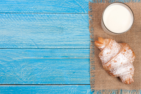sprinkled: glass of milk with croissants on a blue wooden background with copy space for your text. Top view Stock Photo