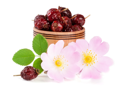 roze: Rosehip flowers with leaf and rosehip berries in a wooden bowl isolated on white background. Stock Photo