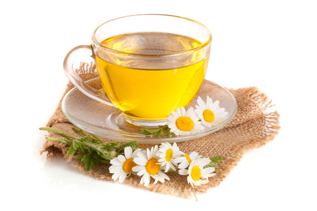 Herbal tea with fresh chamomile flowers on sackcloth isolated on white background. Stock Photo