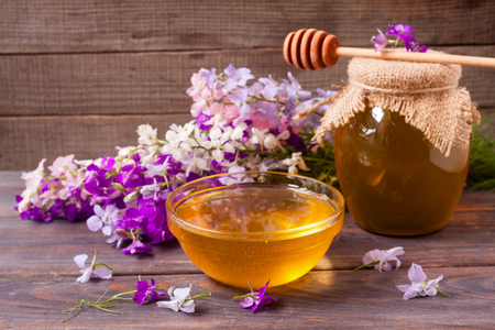 clovers: Jar of honey with wildflowers on a dark wooden background Stock Photo