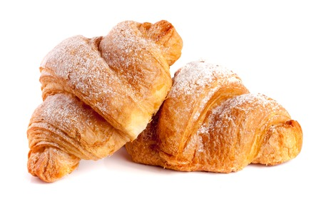 sprinkled: two croissant sprinkled with powdered sugar isolated on a white background closeup