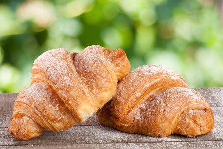two croissant sprinkled with powdered sugar on a wooden board with a blurry garden background