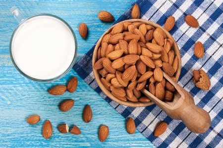 Almond milk in a glass and almonds in a bowl on blue wooden background. Top view Stock Photo