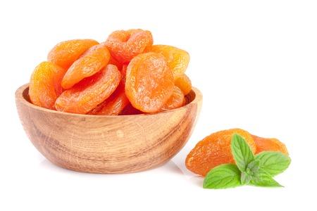 Abricots secs dans un bol en bois avec des feuilles de menthe isolé sur fond blanc Banque d'images - 82191453