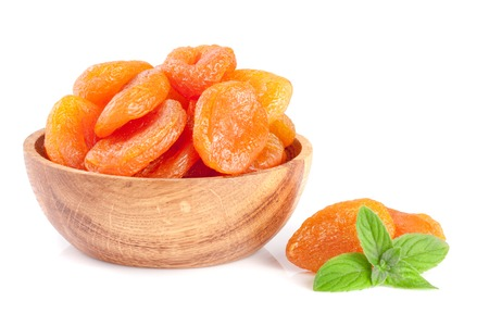 Dried apricots in a wooden bowl with mint leaves isolated on white background Stockfoto