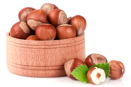 albero nocciolo: Hazelnuts with leaves in a wooden bowl isolated on white background