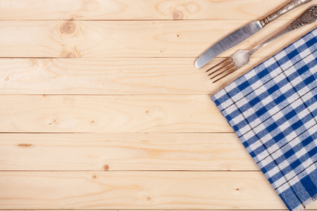checker: blue checkered tablecloth with knife and fork on a light wooden table with copy space for your text. Top view.
