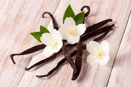 Vanilla sticks with flower and leaf on a white wooden background. Stock Photo