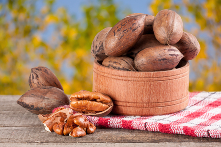 pekan: pecan nuts in a wooden bowl on the old board with blurred garden background.