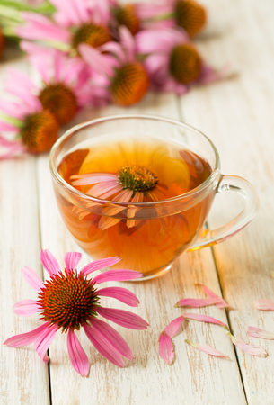 Cup of echinacea tea on white wooden table. Stock Photo