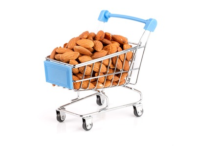 Shopping cart with raw almond isolated on white background