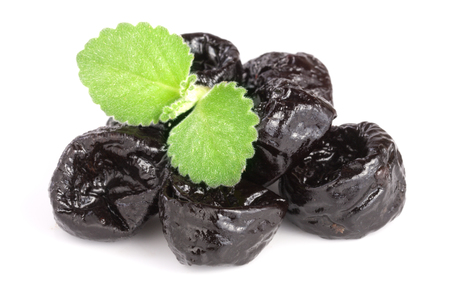 heap of dried plums or prunes with a mint leaf isolated on white background. Imagens - 83068992