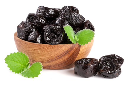 Dried plums or prunes with a mint leaf in wooden bowl isolated on white background Stock Photo