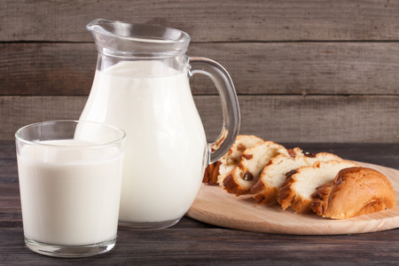 jag: jug and glass of milk with a loaf of bread on a wooden background Stock Photo