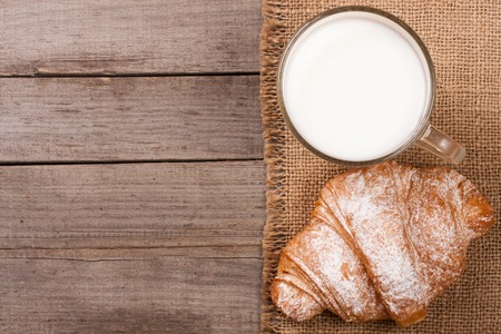 sprinkled: glass of milk with croissants on old wooden background with copy space for your text. Top view