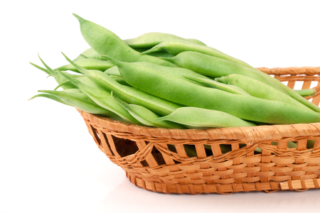 Green beans in a wicker basket isolated on a white background