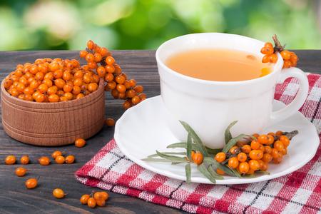 argousier: Thé de baies de l'argousier sur la table en bois avec fond de jardin floue