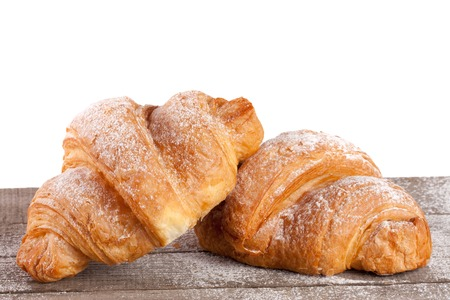 bakery products: two croissant sprinkled with powdered sugar on a wooden table with white background