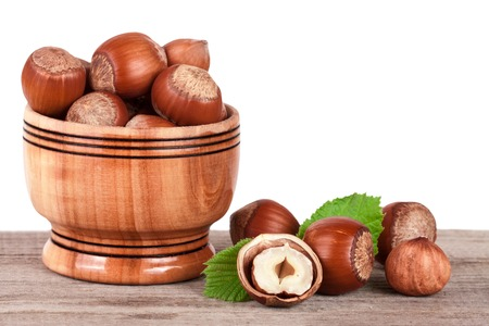 Hazelnuts with leaves in a wooden bowl on a wooden table with a white background. Stock Photo