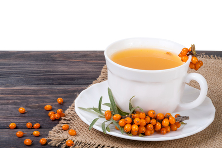 Tea of sea-buckthorn berries with honey on wooden table isolated on white background. Stock Photo