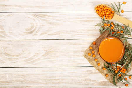 Sea buckthorn juice or tea with berries on a white wooden background with copy space for your text. Top view.