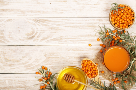 Sea buckthorn juice or tea with honey on a white wooden background with copy space for your text. Top view,