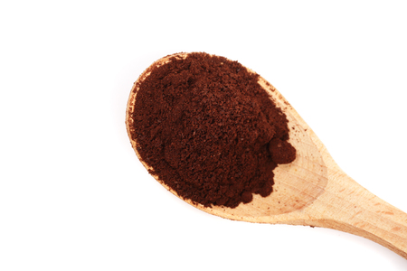 decaf: Wooden Spoon filled with coffee powder isolated on white background. Top view Stock Photo